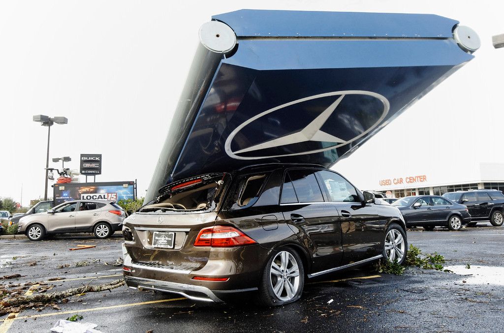 . An automobile is damaged by a Mercedes-Benz dealership sign following a winter storm in Mobile, Alabama, December 20, 2012. The first major winter storm of the year took aim at the U.S. Midwest on Thursday, triggering high wind and blizzard warnings across a widespread area, and a threat of tornadoes in Gulf Coast states to the south. REUTERS/Jon Hauge