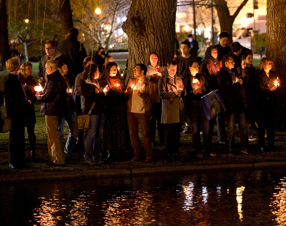 . Mourners gather on the edge of the pond in the Boston Public Gardens for a candle light vigil April 16, 2013 in Boston. A few hundred people gathered to remember the victims of the bombs which exploded during the running of the Boston Marathon.  DON EMMERT/AFP/Getty Images