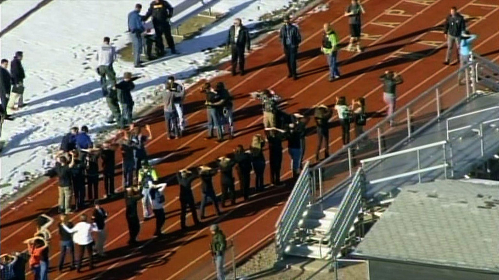 ". In this framegrab taken from video by KCNC television news in Denver, students of Arapahoe High School in Centennial, Colorado, line up to be checked by police at a running track on December 13, 2013 after a shooting at the school. Two students were injured in the shooting incident before the suspected gunman apparently killed himself, the local sheriff said. The suspect was also a student. ""That individual is .. deceased, he apparently killed himself,\"" Arapahoe County Sheriff Grayson Robinson told reporters.     AFP PHOTO / KCNC /AFP/Getty Images"