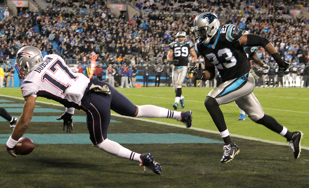 . New England Patriots\' Aaron Dobson (17) drops a pass in the end zone as Carolina Panthers\' Melvin White (23) defends during the second half of an NFL football game in Charlotte, N.C., Monday, Nov. 18, 2013. (AP Photo/Bob Leverone)