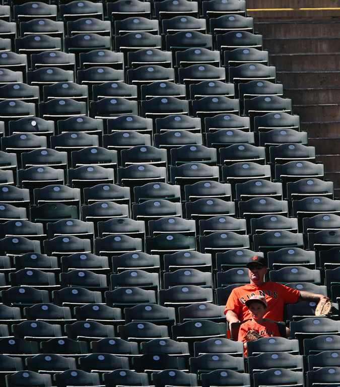 . A pair of San Francisco Giants fans have a section to themselves in left field during the fourth inning of the Colorado Rockies\' 9-2 victory over the Giants in a baseball game in Denver on Wednesday, Sept. 3, 2014. (AP Photo/David Zalubowski)