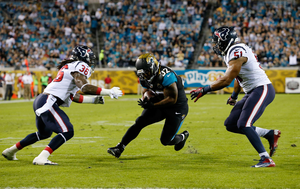 . Maurice Jones-Drew #32 of the Jacksonville Jaguars rushes for yardage against Houston Texan D.J. Swearinger and  Darryl Sharpton #51 of the Houston Texan at EverBank Field on December 5, 2013 in Jacksonville, Florida.  (Photo by Sam Greenwood/Getty Images)