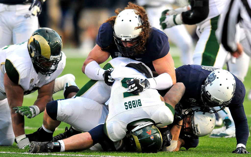 . Colorado State\'s Kapri Bibbs (5) gets tackled by Utah State\'s Zach Vigil with help from Connor Williams and Maurice Alexander during an NCAA college football game, Saturday, Nov. 23, 2013, in Logan, Utah. Utah State won 13-0. (AP Photo/Herald Journal, John Zsiray)