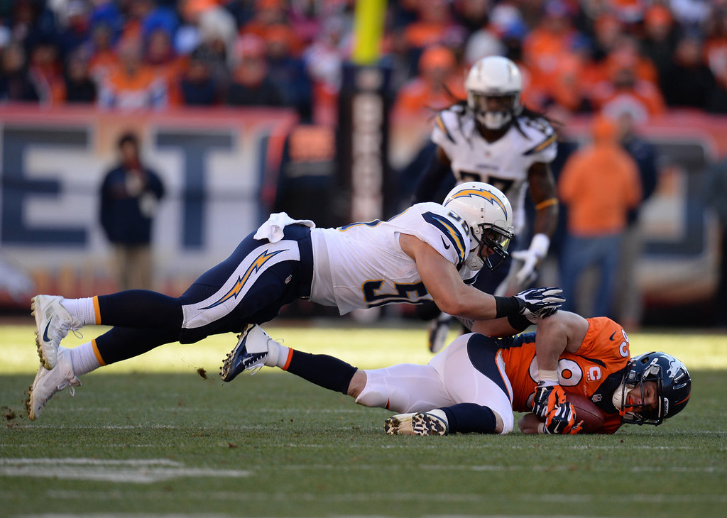 . Denver Broncos wide receiver Wes Welker (83) is taken down by San Diego Chargers inside linebacker Manti Te\'o (50) in the first quarter. The Denver Broncos take on the San Diego Chargers at Sports Authority Field at Mile High in Denver on January 12, 2014. (Photo by Hyoung Chang/The Denver Post)