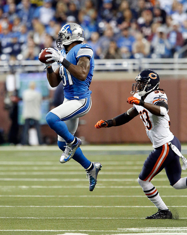 . Detroit Lions wide receiver Calvin Johnson (81) makes a reception while defended by Chicago Bears cornerback Charles Tillman (33) during the first quarter of an NFL football game at Ford Field in Detroit, Sunday, Dec. 30, 2012. (AP Photo/Duane Burleson)