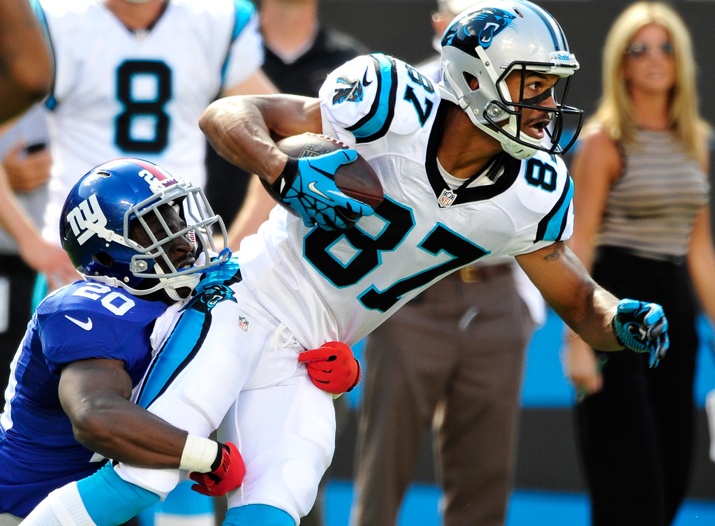 . Domenik Hixon #87 of the Carolina Panthers stretches for extra yardage after making a first down catch against Prince Amukamara #20 of the New York Giants during play at Bank of America Stadium on September 22, 2013 in Charlotte, North Carolina. The Panthers won 38-0.  (Photo by Grant Halverson/Getty Images)
