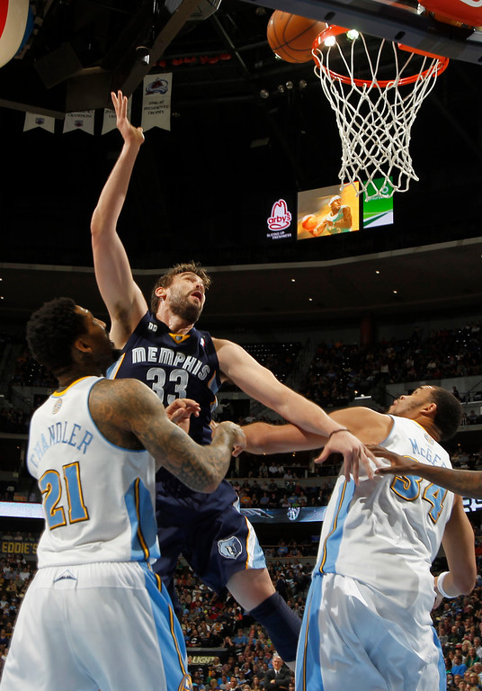 . Memphis Grizzlies center Marc Gasol, center, of Spain, shoots between Denver Nuggets forwards Wilson Chandler, left, and JaVale McGee in the first quarter of an NBA basketball game in Denver, Friday, March 15, 2013. (AP Photo/David Zalubowski)