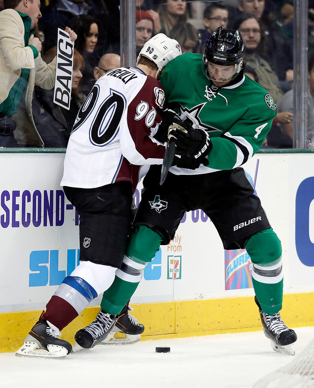 . Dallas Stars\' Brenden Dillon (4) and Colorado Avalanche\'s Ryan O\'Reilly (90) compete for control of the puck behind the net in the second period of an NHL hockey game, Tuesday, Dec. 17, 2013, in Dallas. (AP Photo/Tony Gutierrez)