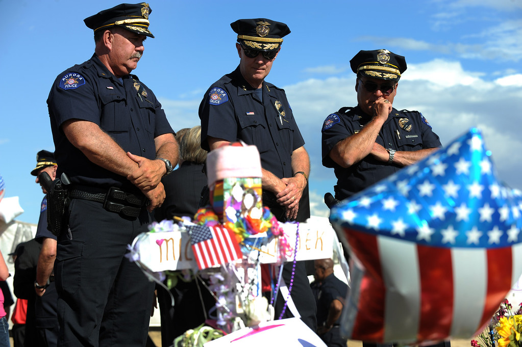 . From left to right, Aurora Police Commander Kevin Flynn, Captain Bob Stef, and Commander Jack Daluz take a moment to reflect on the tragic night of the shooting as well as to look at the growing memorial. The senior leadership of the Aurora Police Department, the Aurora Fire Department and the Denver Field Office of the Federal Bureau of Investigations gathered at the memorial site to honor the victims on July 25th, 2012. Helen H. Richardson, The Denver Post