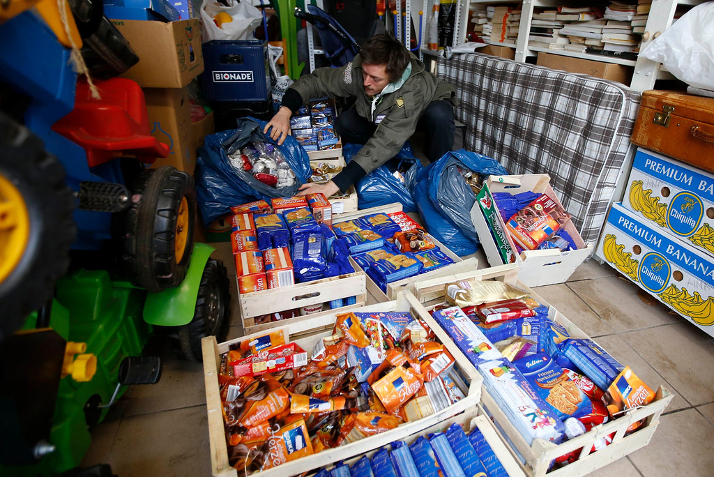 . Raphael Fellmer, a supporter of the foodsharing movement shows Christmas biscuits collected from waste bins of supermarket at his home in Berlin, January 31, 2013. Foodsharing is a German internet based platform where individuals, retailers or producers have the possibility of offering surplus food to consumers for free. Picture taken January 31.   REUTERS/Fabrizio Bensch