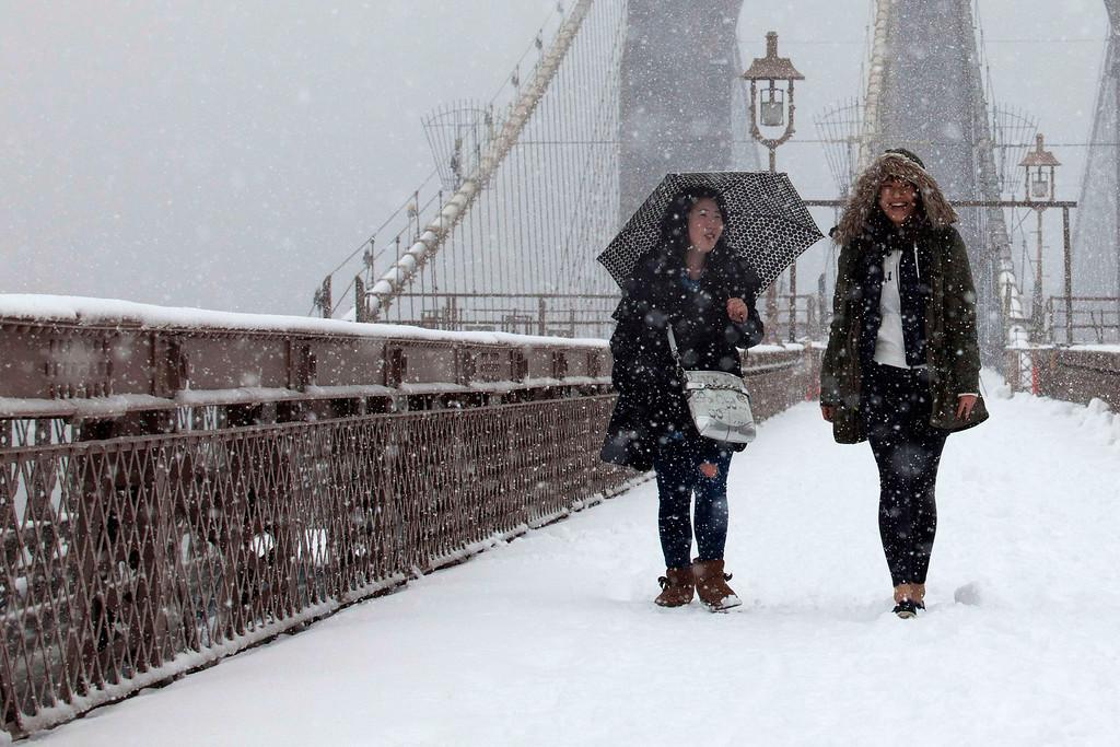 . Women walk on the Brooklyn Bridge during a snowstorm in New York, March 8, 2013.  REUTERS/Eduardo Munoz
