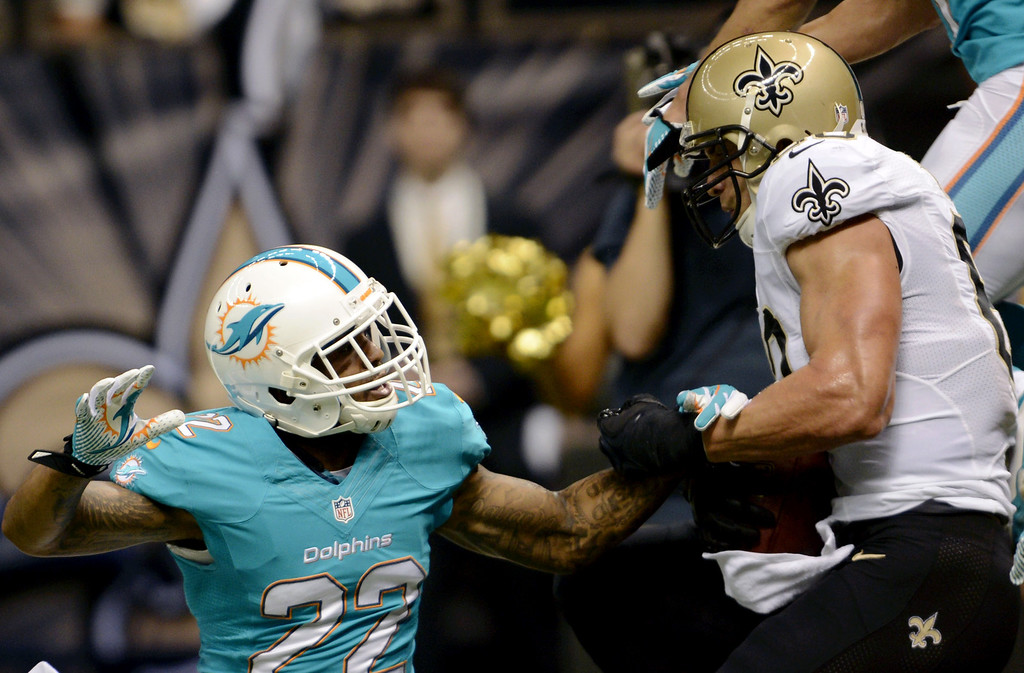 . New Orleans Saints tight end Jimmy Graham (80) pulls in a touchdown reception over Miami Dolphins cornerback Jamar Taylor (22) in the first half of an NFL football game in New Orleans, Monday, Sept. 30, 2013. (AP Photo/Bill Feig)