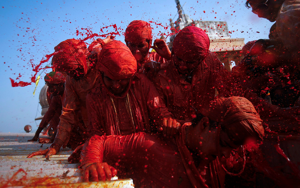 ". Hindu devotees throw coloured water at each other at a temple during ""Lathmar Holi\"" at the village of Barsana in the northern Indian state of Uttar Pradesh March 21, 2013. In a Holi tradition unique to Barsana and Nandgaon villages, men sing provocative songs to gain the attention of women, who then \""beat\"" them with bamboo sticks called \""lathis\"". Holi, also known as the Festival of Colours, heralds the beginning of spring and is celebrated all over India. REUTERS/Vivek Prakash"