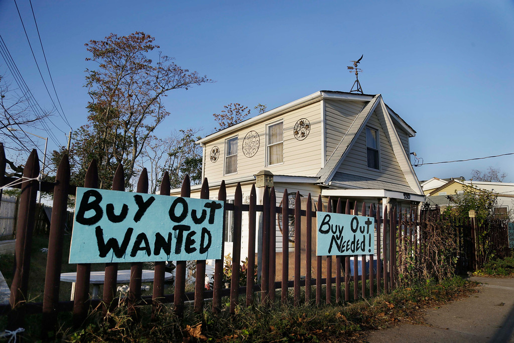 ". Signs asking for a ""buy out\"" hang in front of a home damaged by Superstorm Sandy in the Ocean Breeze section of Staten Island, New York, Tuesday, Oct. 29, 2013.  (AP Photo/Seth Wenig)"