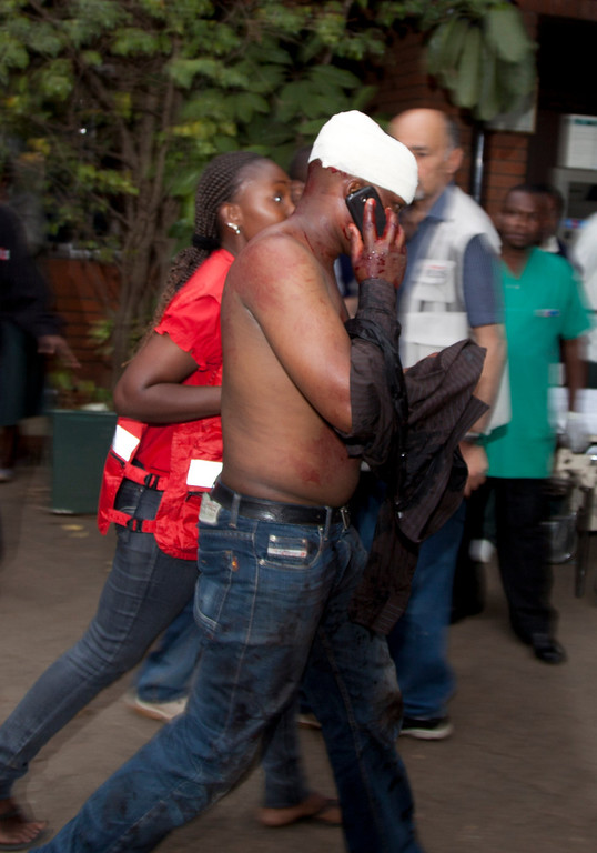 . An injured person makes a phone call as he is helped on his arrival at the Aga Khan Hospital in Nairobi after an attack at the Westgate Mall, an upscale shopping mall in Nairobi, Kenya Saturday Sept. 21, 2013, where shooting erupted when armed men staged an attack.  (AP Photo/Jason Straziuso)