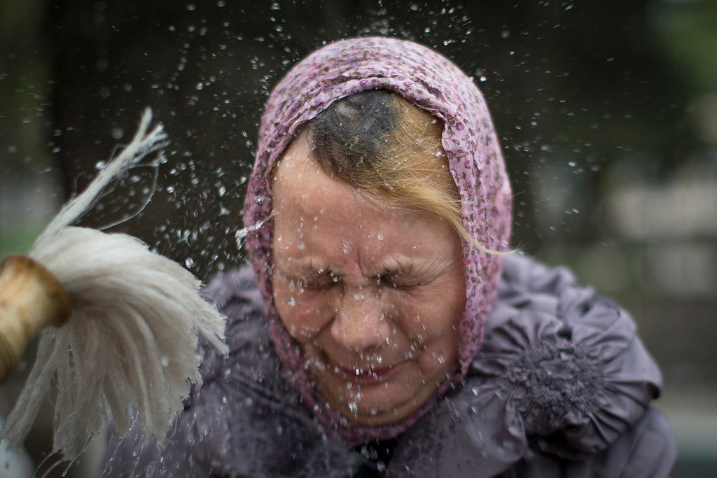 . A a woman reacts as an Orthodox priest blesses her and traditional Easter cakes and painted eggs prepared for an Easter celebration, at a church in Slovyansk, Ukraine, Saturday, April 19, 2014. Pro-Russian insurgents defiantly refused Friday to surrender their weapons or give up government buildings in eastern Ukraine, despite a diplomatic accord reached in Geneva and overtures from the government in Kiev.(AP Photo/Alexander Zemlianichenko)