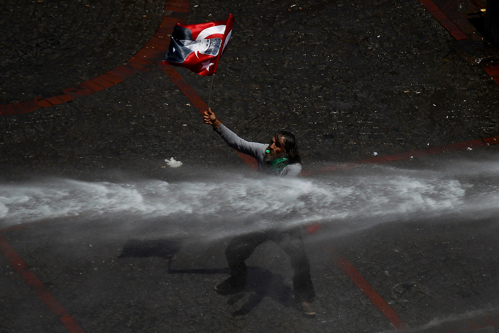 . A protester holding a Turkish flag stands in front of a police water canon during clashes in Taksim square in Istanbul, Tuesday, June 11, 2013.  (AP Photo/Kostas Tsironis)