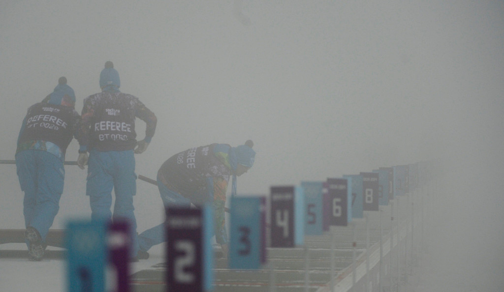 . Venue referees walk along the shooting range heavy fog prior to the Men\'s Biathlon 15km competition at Laura Cross Country and Biathlon Center at the Sochi 2014 Olympic Games, Krasnaya Polyana, Russia, 16 February 2014. Men\'s 15km mass start has been postponed to Monday, 17 February it was announced.  EPA/FILIP SINGER