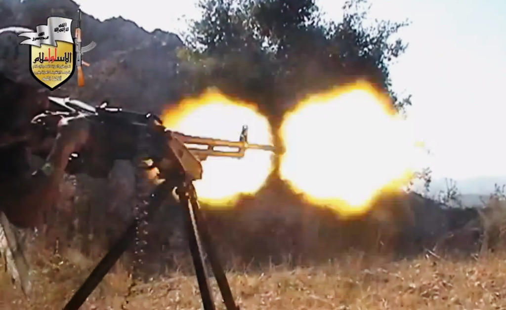 . In this file image taken from Sunday, Aug. 11, 2013, video obtained from the Shaam News Network, which has been authenticated based on its contents and other AP reporting, a rebel fighter fires a gun in a valley in an unidentified location in Latakia province, Syria. Jihadi-led rebel fighters in Syria killed at least 190 civilians and abducted more than 200 during an offensive against pro-regime villages, committing a war crime, an international human rights group said Friday, Oct. 11, 2013. (AP Photo/Shaam News Network via AP Video, File)