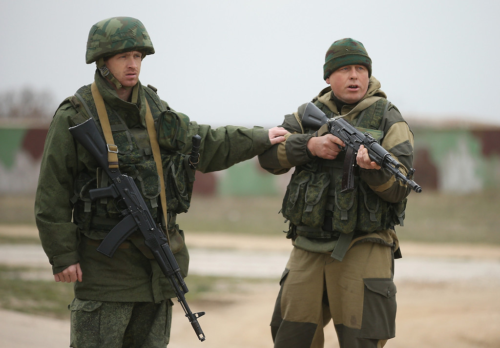 . A soldier under Russian command restrains a colleague after he fired his weapon into the air and screamed orders to turn back at an approaching group of over 100 unarmed Ukrainian troops at the Belbek airbase, which the Russian troops are occupying, in Crimea on March 4, 2014 in Lubimovka, Ukraine.  (Photo by Sean Gallup/Getty Images)