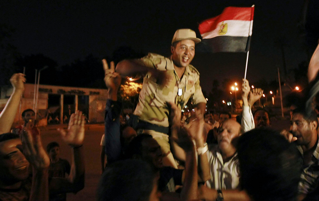 ". An army soldier (C) cheers with protesters, who are against Egyptian President Mohamed Mursi, as they dance and react in front of the Republican Guard headquarters in Cairo July 3, 2013. Egypt\'s armed forces overthrew elected Islamist President Mohamed Mursi on Wednesday and announced a political transition with the support of a wide range of political, religious and youth leaders. A statement published in Mursi\'s name on his official Facebook page after head of Egypt\'s armed forces General Abdel Fattah al-Sisi\'s speech said the measures announced amounted to ""a full military coup\"" and were \""totally rejected\"".  REUTERS/Louafi Larbi"