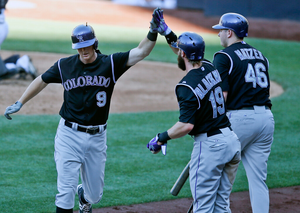 . Colorado Rockies\' DJ Lemahieu high fives with Charlie Blackmon after his solo home run against the San Diego Padres in the fifth inning of a baseball game Wednesday, Aug. 13, 2014, in San Diego. (AP Photo/Lenny Ignelzi)