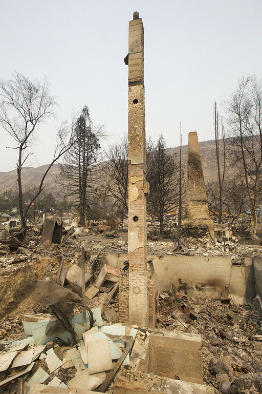. A pair of chimneys stand amid the rubble of a neighborhood destroyed by fire  July 20, 2014 in Pateros, Washington on July 17. Several fires throughout the state have destroyed hundreds of home forced evacuations and continue to threaten more communities. (Stephen Brashear/Getty Images)