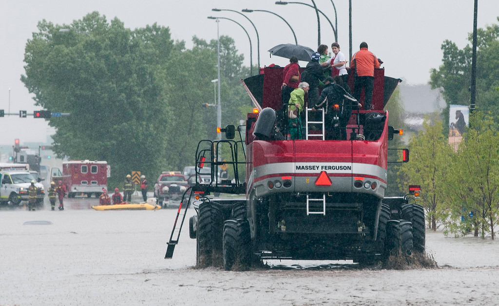 . People travel from a co-op store on a combine harvester in High River in Alberta province June 20, 2013. A state of emergency has been issued for the town of High River, which is being evacuated due to floods. REUTERS/Mike Sturk