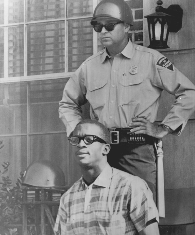 . A helmeted campus policeman stands by as James Hood leaves his dormitory, Palmer Hall, for class at the University of Alabama at Tuscaloosa today. 1963