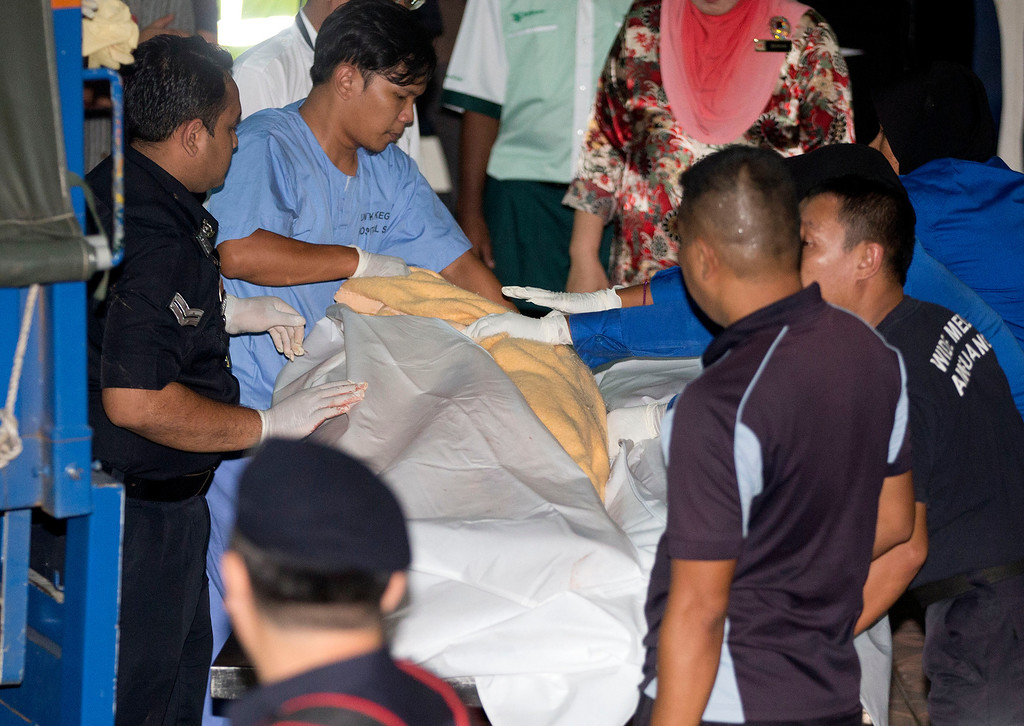 . Police and hospital staff remove a body from a van outside the Kuala Lumpur General Hospital after a bus carrying tourists and local residents fell into a ravine near the Genting Highlands, about an hour\'s drive from Kuala Lumpur, Malaysia, Wednesday, Aug. 21, 2013. (AP Photo/Mark Baker)
