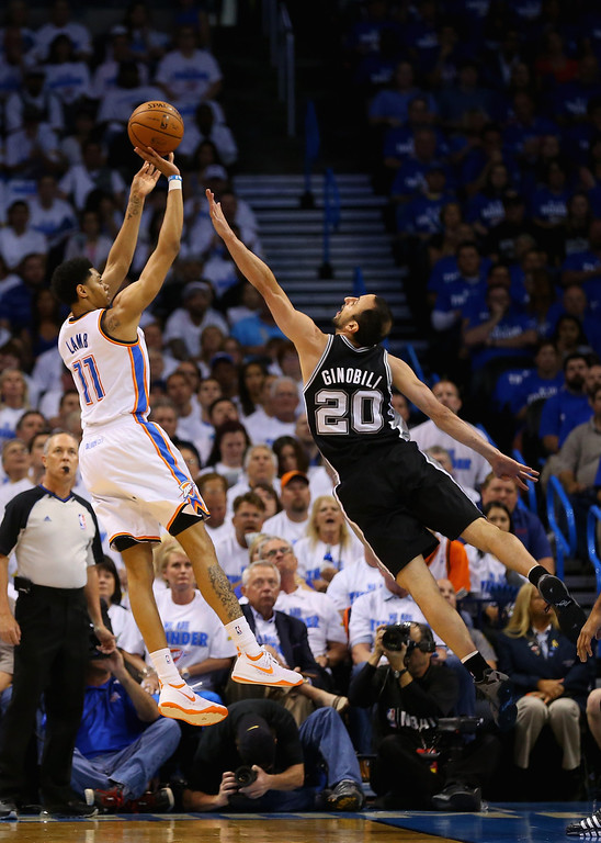. OKLAHOMA CITY, OK - MAY 27: Jeremy Lamb #11 of the Oklahoma City Thunder shoots against Manu Ginobili #20 of the San Antonio Spurs in the first half during Game Four of the Western Conference Finals of the 2014 NBA Playoffs at Chesapeake Energy Arena on May 27, 2014 in Oklahoma City, Oklahoma. (Photo by Ronald Martinez/Getty Images)