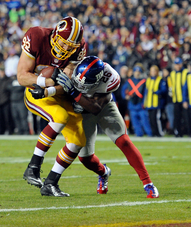. Washington Redskins tight end Logan Paulsen (82) is hit by New York Giants strong safety Antrel Rolle (26), but gets across the goal line for a touchdown during the first half of an NFL football game Sunday, Dec. 1, 2013, in Landover, Md. (AP Photo/Nick Wass)