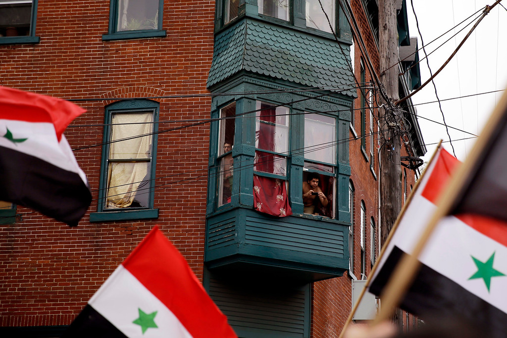. Residents watch from their windows as members of the local Syrian community rally against the United States\' involvement in Syria, Friday, Aug. 30, 2013, in Allentown, Pa. President Barack Obama says he hasn\'t made a final decision about a military strike against Syria_but is considering a limited and narrow action in response to a chemical weapons attack that he says Syria\'s government carried out last week. (AP Photo/Matt Slocum)