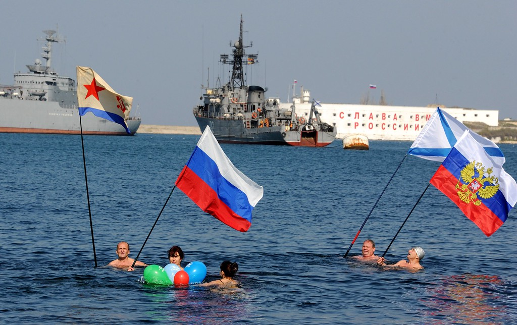 . People swimming in the cold waters of the harbor of Sevastopol hold Russian national and navy flags to mark their support for Russian forces, as a Russian Navy ship remains stationed in the background, on March 15, 2014. Ukraine braced for a breakaway vote in Crimea as deadly violence flared again in the ex-Soviet country\'s tinderbox east amid the biggest East-West showdown since the Cold War.  AFP PHOTO / VIKTOR DRACHEV/AFP/Getty Images