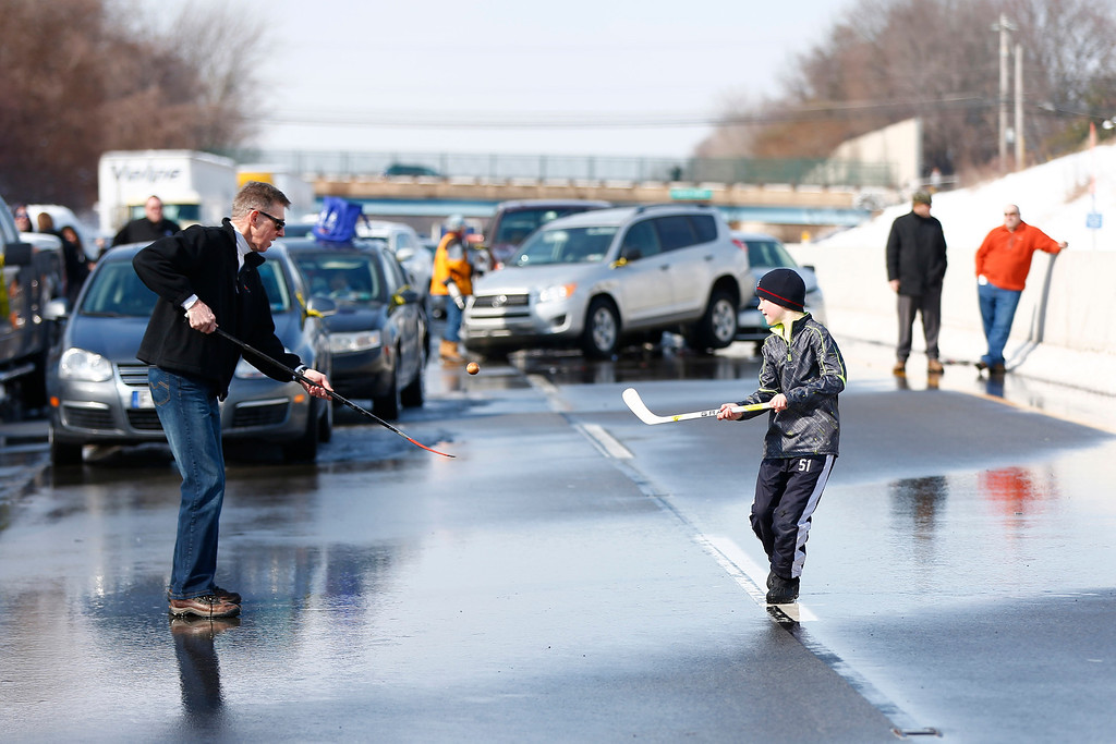 . A father and son pass the time as while they are stuck in traffic near where vehicles are piled up in an accident, Friday, Feb. 14, 2014, in Bensalem, Pa.  (AP Photo/Matt Rourke)