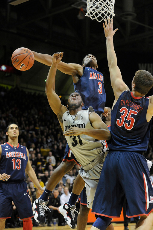 . BOULDER, CO. - FEBRUARY 14: Wildcats guard Kevin Parrom (3) blocked an attempt from Buffs guard Jeremy Adams (31) in the first half. The University of Colorado men\'s basketball team hosted Arizona Thursday night, February 14, 2013 at the Coors Event Center in Boulder. (Photo By Karl Gehring/The Denver Post)