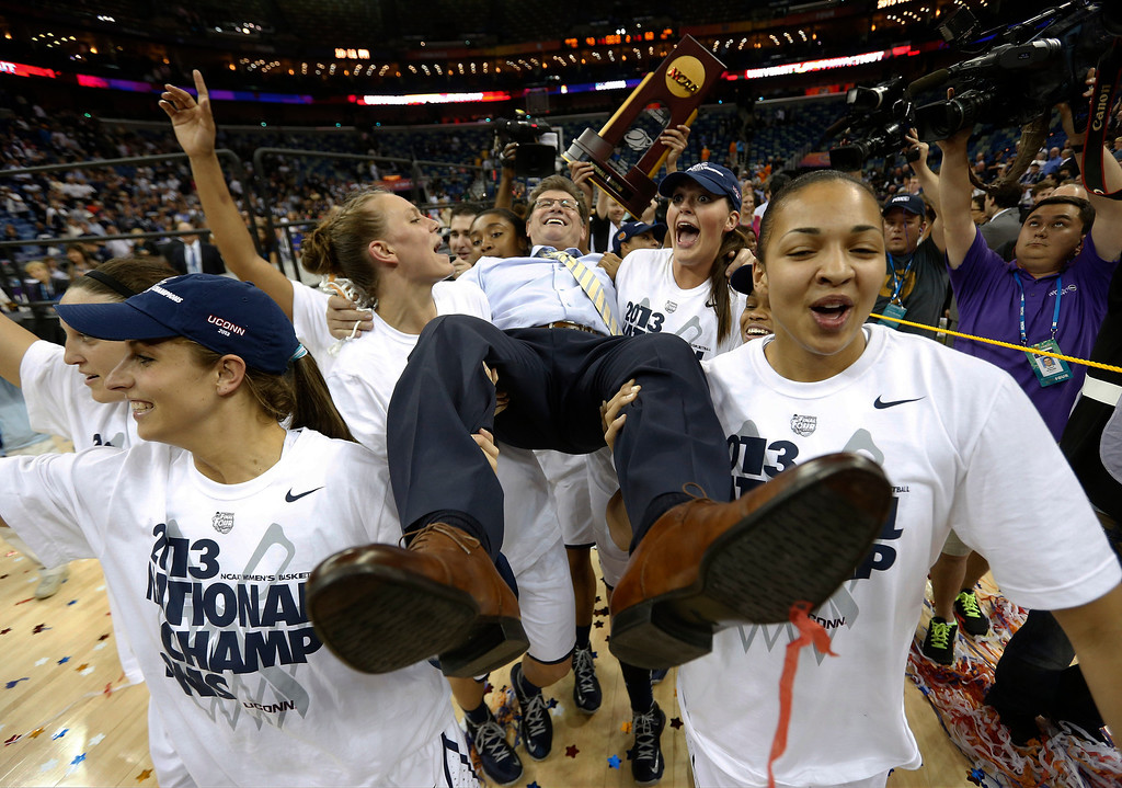 . Connecticut players celebrate as they carry their head coach Geno Auriemma after defeating Louisville 93-60 in the national championship game of the women\'s Final Four of the NCAA college basketball tournament, Tuesday, April 9, 2013, in New Orleans. (AP Photo/Dave Martin, File)
