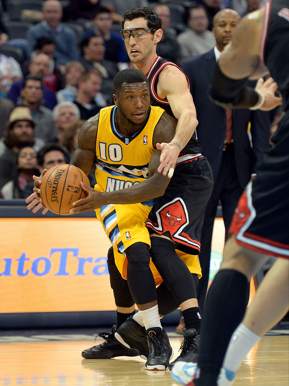. Denver Nuggets point guard Nate Robinson (10) looks to make a pass as he gets bumped by Chicago Bulls shooting guard Kirk Hinrich (12) during the first quarter November 21, 2013 at Pepsi Center. (Photo by John Leyba/The Denver Post)