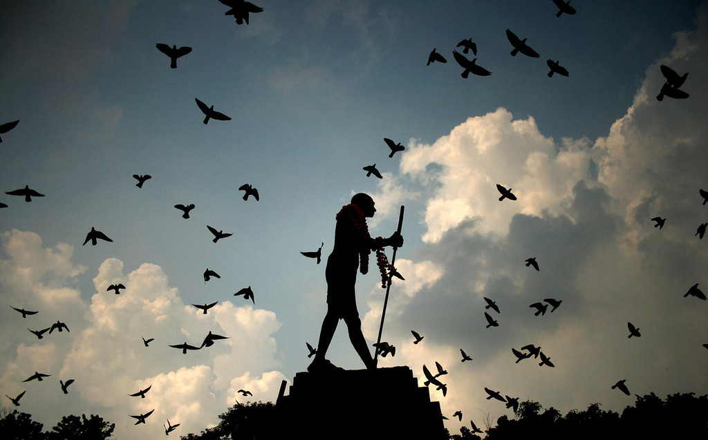 . Pigeons fly behind a silhouetted statue of Mahatma Gandhi adorned with garlands on Gandhi\'s birth anniversary in Amritsar, India Wednesday, Oct. 2, 2013. (AP Photo/Sanjeev Syal)