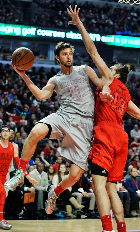 . Houston Rockets\' Chandler Parsons (25) looks to pass around Chicago Bulls\' Joakim Noah (13) during the first quarter of an NBA basketball game in Chicago, Tuesday, Dec. 25, 2012. (AP Photo/Paul Beaty)