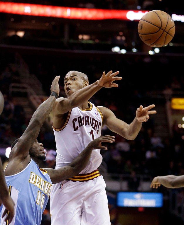 . Cleveland Cavaliers\' Jarrett Jack (1) passes in front of Denver Nuggets\' Nate Robinson (10) during the fourth quarter of an NBA basketball game on Wednesday, Dec. 4, 2013, in Cleveland. The Cavaliers won 98-88. (AP Photo/Tony Dejak)
