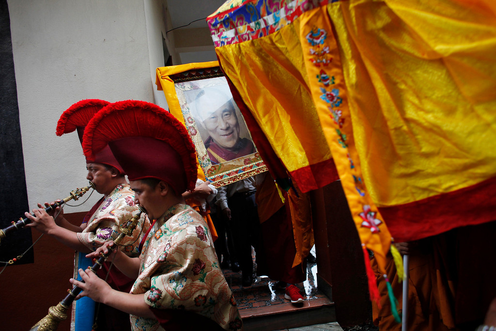 . Tibetan Monks play tradition instruments as other carry a portrait of their spiritual leader the Dalai Lama during celebrations to mark his birthday in Katmandu, Nepal, Saturday, July 6, 2013. The Tibetan leader turned 78. (AP Photo/Niranjan Shrestha)