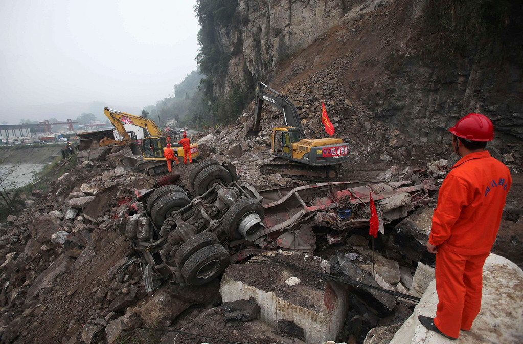 . A rescuer looks on as excavators clean up a road which is blocked by a landslide after Saturday\'s earthquake, in Baoxing county, Sichuan province April 22, 2013.REUTERS/China Daily
