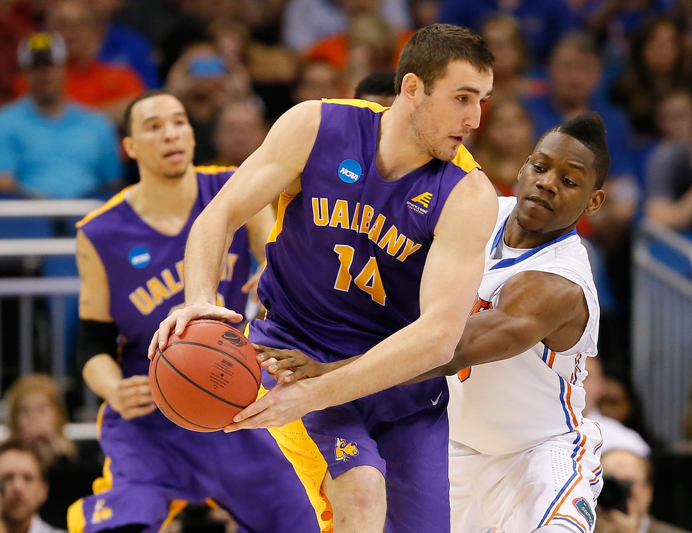 . ORLANDO, FL - MARCH 20:  Sam Rowley #14 of the Albany Great Danes with the ball against Will Yeguete #15 of the Florida Gators in the first half during the second round of the 2014 NCAA Men\'s Basketball Tournament at Amway Center on March 20, 2014 in Orlando, Florida.  (Photo by Kevin C. Cox/Getty Images)