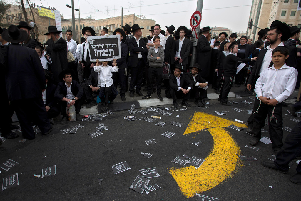 """. Ultra-Orthodox Jews rally in a massive show of force against plans to force them to serve in the Israeli military, blocking roads and paralyzing the city of Jerusalem, Sunday, March 2, 2014. The widespread opposition to the compulsory draft poses a challenge to the country, which is grappling with a cultural war over the place of the ultra-Orthodox in Israeli society. With secular Jews required to serve, the issue is one of the most sensitive flashpoints between Israel\'s secular majority and its devout minority. Hebrew sign reads: \""""The holy bible will win.\"""" (AP Photo/Sebastian Scheiner)"""