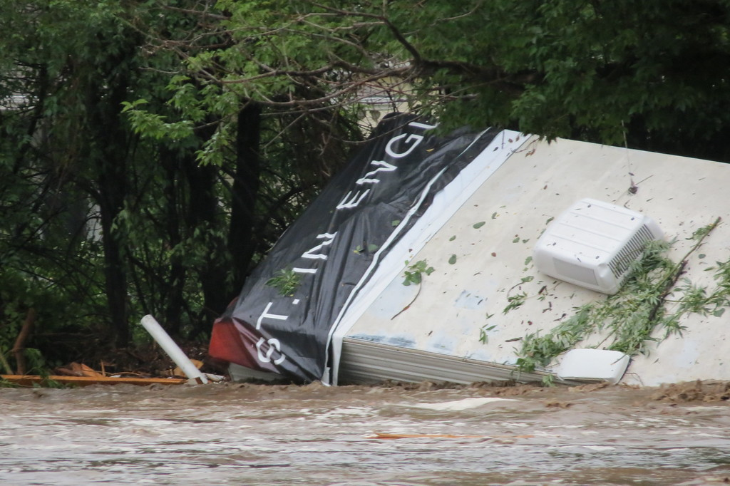 . The Big Thompson River traps a trailer in the mid-river raging current as it floods down through Marianna Butte golf course and the surrounding neighborhoods on Friday, September 13th. Photo by Mike Garcia