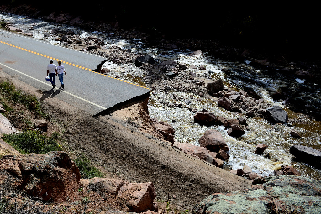 . Denise Stewart holds hands with John Lucero as they walk back towards Pinewood Springs during a tour to look at the damage caused by recent flooding in the area on U.S. Highway 36 between Lyons and Pinewood Springs. Pavement is missing in many section of the road that connects Lyons to Estes Park. (Photo by AAron Ontiveroz/The Denver Post)