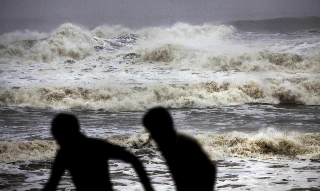 . Indian people run for shelter following a cyclone warning at the Bay of Bengal coast in Gopalpur beach in Ganjam district about 200 kilometers  (125 miles) from the eastern Indian city Bhubaneswar, India, Saturday, Oct. 12, 2013. Hundreds of thousands of people living along India\'s eastern coastline were taking shelter Saturday from a massive, powerful cyclone Phailin that was set to reach land packing destructive winds and heavy rains. (AP Photo/Biswaranjan Rout)