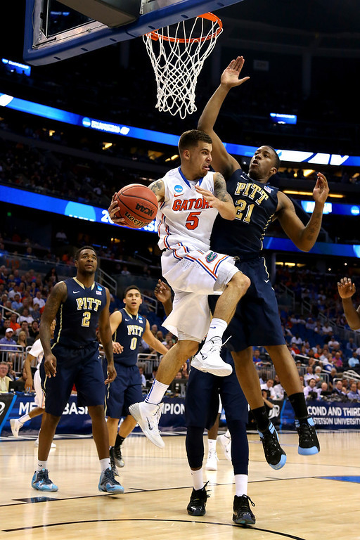 . Scottie Wilbekin #5 of the Florida Gators looks to pass against Lamar Patterson #21 of the Pittsburgh Panthers in the first half during the third round of the 2014 NCAA Men\'s Basketball Tournament at Amway Center on March 22, 2014 in Orlando, Florida.  (Photo by Mike Ehrmann/Getty Images)