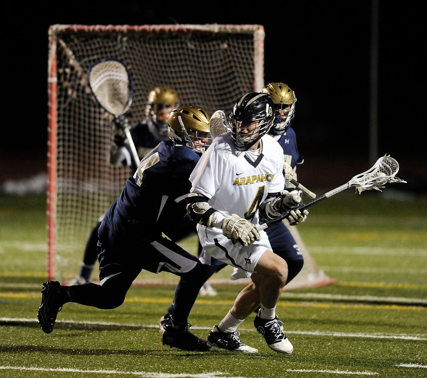 . LITTLETON, CO. - APRIL 10: Warriors senior middie Tyler Lampard (4) looked for an opening in the fourth quarter. The Mullen High School boy\'s lacrosse team defeated Arapahoe 8-7 Wednesday night, April 10, 2013. Photo By Karl Gehring/The Denver Post)